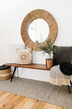 Insane oversize round wood mirror with a midcentury modern style bench and cozy pillows and throws to add warmth The post oversize round wood mirror with a midcentury modern style bench and ..