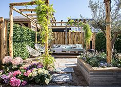 In deze zuidelijke zomertuin tuin zijn verschillende zitjes gemaakt om te kunnen relaxen en eten. Ook staat er een stoere, robuuste overkapping. Er zijn twee borderbakken gevuld met kleurrijke en mediterrane beplanting en als kers op de taart; een buitenkeuken! Met deze kleurrijke tuin ben je helemaal klaar voor de zomer.