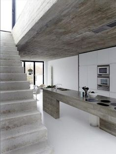 Méchant Design: mix up concrete and white..verrrry spartan kitchen & stairs..way sleek