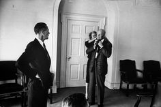 PRESIDENT DWIGHT D. EISENHOWER's secretary, ANN WHITMAN, helps the President don a borrowed tie on the morning of JFK's Inauguration.  --  January 20, 1961