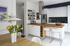 A small spot for wine storage is built-in below the white and wood island in this modern kitchen.