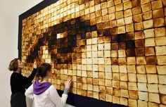 Visitors take a close look at an artwork by German artist Arne Felix Magold during an exhibition in Hamburg. The work is made up of 612 slices of toasted bread