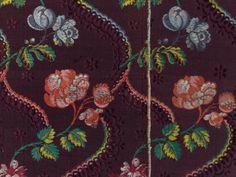 Manches démontées d'une robe en lampas lancé, Tours vers 1760. Méandres fleuris bleu, rouge et jaune sur fond armuré en rubans et fleurons de couleur tête-de-nègre. - On joint un fragment d'un autre lampas très proche (sur carton) et un beau document d'un lampas broché de fleurs multicolores sur fond tête de nègre armuré.