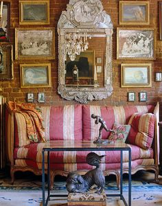 The 18th century Italian sofa and Venetian mirror in this living room contrast with the exposed brick wall behind