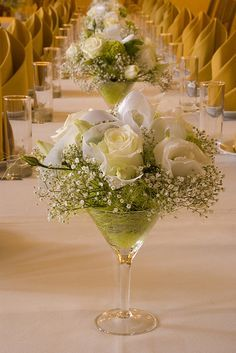 Creative White Roses and Baby\'s Breath Centerpieces in Martini Glasses ~ Your choice of colour of Roses. The Martini Glasses have a lovely shape and all in a line the effect is simple but beautiful. You could alternate the Rose colors, like first Glass white Roses, next glass deep peach ~ I think you know what I mean. Wonderfully simple idea and saves a bit of cash on floral arrangements!