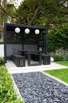 Enclosing this is a timber structure including an integral table and two benches, which will provide further opportunity for al fresco dining. The structure is partially covered with a timber and stainless steel mesh roof to prevent the mulberry bush berries marking the table. Two sides of the structure have alcove shelving to help create the impression of an outdoors room as well as giving a nod towards the Japanese theme. #outsidedining #pergola #japanesegarden