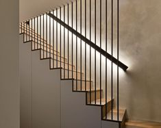 These modern wood stairs have a handrail with hidden lighting, and a floor-to-ceiling steel rod safety barrier. Wood Stair Handrail, Wall Mounted Handrail, Wood Stairs, Handrail Ideas, Steel Handrail, Hidden Lighting, Stair Lighting, Stairs Handle, Staircase Design