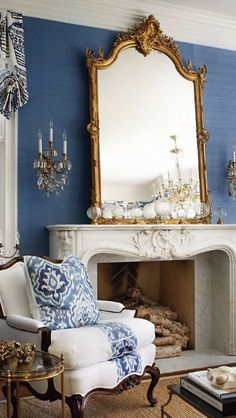 Rich blue wall, lovely fireplace, gilded mirror, Bergere chair.