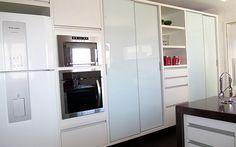 Cozinha com portas de correr em vidro branco