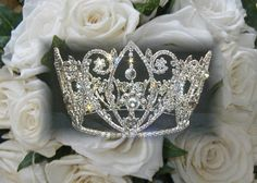 This Glorious Crown Headpiece makes for a stunning finishing touch for Pageants, Bride's wedding day or Quinceanera. The dazzling crown stands 5 inches tall by 6 inches in diameter. Crown is plated in sterling silver with rhinestones going completely around the crown. There are 4 rings in the center to assist with bobby pins in holding the crown to the head.