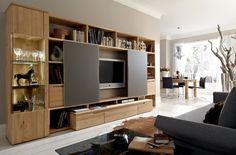 A, acabado de madera ricamente grano rústico destaca este gran centro de entretenimiento que se extiende por la pared en esta vida moderna.