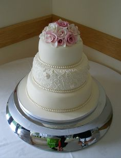 Dusky pink and ivory roses, pearls and piping adorn this three tier