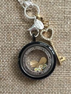 Origami Owl loves their mixed metals. Large black locket face with gold key, and silver chain.  Love is patient love is kind window plate