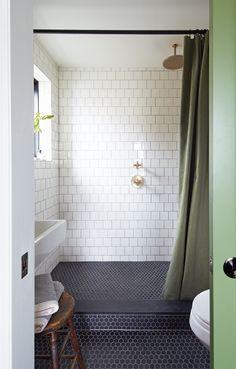 En contraste avec les matériaux rétro, comme le marbre et le laiton, voyez comment la propriétaire a choisi des éléments modernes tels que les fenêtres peintes en noir et les œuvres d'art, afin de réaliser une salle de bain charmante, à petit budget.