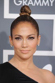 Jennifer Lopez sofisticó su look para la última edición de los Premios Grammy, y añadió a su túnica negra con escote asimétrico y amplia abertura hasta la cadera de Anthony Vaccarello, un limpio y pulido moño bun.