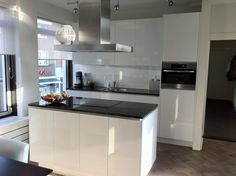 Modern white kitchen with island. In glossy white with black natural counters