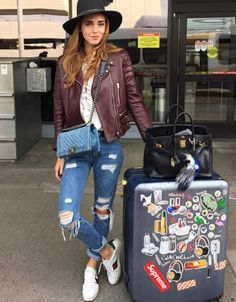 Chiara Ferragni wears a lace-up top, leather jacket, boyfriend jeans, Gucci sneakers, a fedora, and Chanel bag