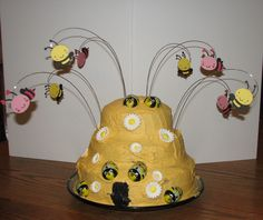 Gender Revel Party - Bee Theme Beehive Cake - Used cricut cartridge Create a Critter & Create a Critter 2, Duff cake mix (white), butter cream recipe (icing) Duff food coloring (gold & black), Duff cake wires, Wilton white daisy candies. Solid chocolate bumble bee's from Sweet Indulgence, Monroe Wa.