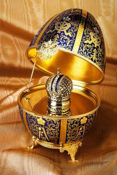 "Though NON-MUSICAL, this is one of the most spectacular Faberge Eggs. The Twelve Monogram Egg is a reproduction of a 1895 classic. It is hand-painted Limoges porcelain and the ""surprise"" inside is a 24k gold-plated crown. Hidden inside the crown is an enamel guilloches pendant. This is a limited edition piece -- 8"" tall."