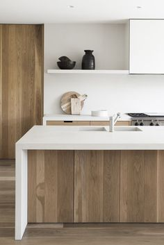 simple contemporary kitchen. white worktops, wooden cabinets