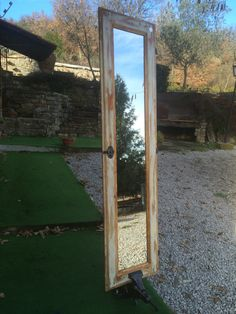 Scuro di vecchia finestra trasformato in specchiera con basamento vecchia morsa da banco.