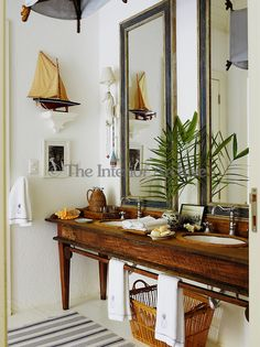 Another guest bathroom is decorated in a nautical theme with a pair of antique mirrors
