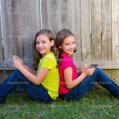 Hermana gemela niñas jugando tablet pc sentados en el césped del ...