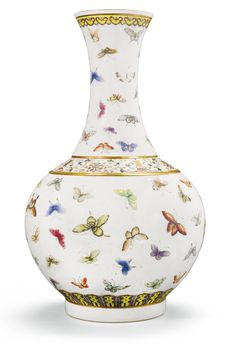 A FAMILLE-ROSE 'HUNDRED BUTTERFLIES' BOTTLE VASE GUANGXU MARK AND PERIOD the globular body moulded with a raised fillet to the shoulder, rising from a straight foot to a tall waisted neck flaring at the rim, the exterior brightly enamelled with the 'hundred butterflies' design, divided by a wide band of gilt shou characters interspersed with stylised lotus sprigs, the