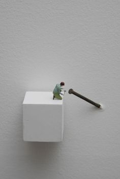 "Liliana Porter, ""Forced Labor (Nail)"", 2008,  figurine on wooden base and nail on wall"