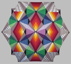 Surprise for Werner Quilt by Carol Anne Grotrian: Hexagonal kaleidoscope pattern using a full color wheel, offset with silver lame.