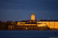 taivasalla.net - Under the Open Sky - May 2014. Helsinki: The lighthouse of Suomenlinna and other buildings on the Suomenlinna islands bathing in evening sunlight in a view from the shore of Kaivopuisto district.
