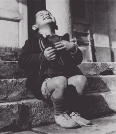 A 6-year-old Austrian orphan beams with joy while clasping a new pair of shoes given to him by the American Red Cross, 1945