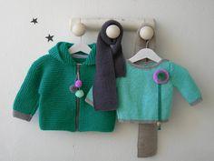 Cazadora con capucha para bebe en verde, con puños y pompón en gris plata combinado con jersey básico cuelga-chupete en color verde claro y agua. Para no pasar frío este invierno que mejor que una bufanda también en color gris a conjunto o en color azul vaquero.