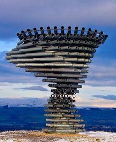 The Singing Ringing Tree | Atlas Obscura. The Singing Ringing Tree is aptly named. A 3-meter-tall, wind-powered musical sculpture made of galvanized steel pipes, it stands high above the English town of Burnley. The pipes swirl to form the shape of a tree bent and blown by the wind, and produce an eerie, melodious hum as the constant wind on Crown Point drifts through them. The Singing Ringing Tree's pipes are used for both aesthetic qualities as well as for tuning, with their sound varied…