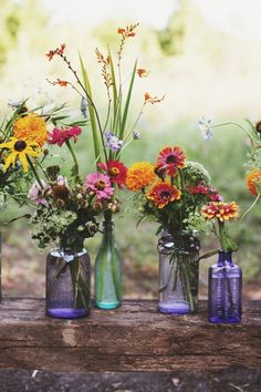 Vibrant wildflowers in light blue vases. The wedding at the link is worth checking out too.