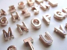 Buy alphabet magnets and spray paint them metallic