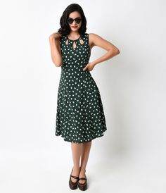 Let your ensemble sing, darlings! A 1940s inspired dress complete in a breezy swing silhouette and patterned in a radiant heart print set against deep forest green. A slightly gathered empire bodice boasts teardrop cut outs, an easy fitted sleeveless desi