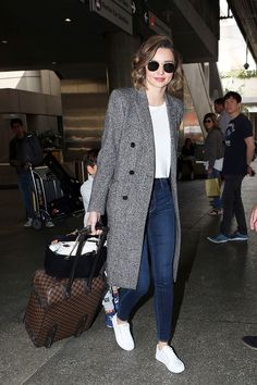 Miranda Kerr strolls out of the airport in her go-to outfit combo. The supermodel styled a long over coat over a white tee with the Bombshell Skinny in Empire and crisp white sneakers. Estilo Miranda Kerr, Miranda Kerr Style, Sneaker Outfits, T-shirt Und Jeans, Pijamas Women, Winter Outfits, Casual Outfits, Fashion Outfits, Fashion Purses