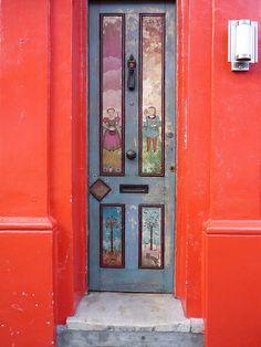 An Ornate Narrow Door, Set Deeply In A Bright Red Wall. Notting Hill, London