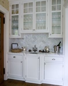 Built in glassed front cabinetry and herringbone tiled backslash