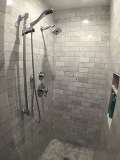 Marble tile lends a #classic aesthetic to this large, open shower.