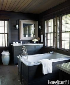 Sheathed in dark-stained pine with simple cabinetry, the master bathroom has the look of a rustic retreat.