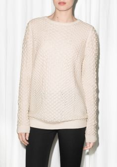 This merino wool sweater has an oversized, relaxed look and a raised knit design.