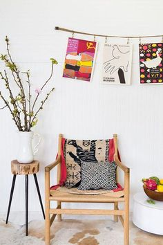 Bold and colorful art prints strung against modern white interior