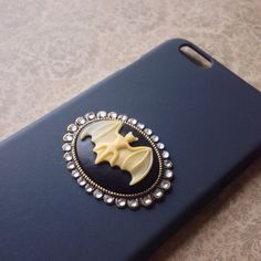 iPhone 6plus/6plus black bat cameo phone case This phone case is for the iPhone 6 Plus/6s plus+. Case is matte black. Center has a bat cameo made from resin (cream on black). Cameo setting is brass and is adorned with rhinestones. ( If you prefer different rhinestone colors message me, I have a lot of colors to choose from! Accessories Phone Cases