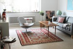 Lovely living room. Nice colors in the carpet and I love the grey chair & couch