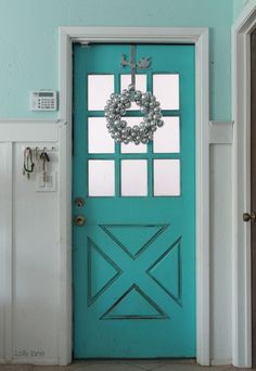 Simple silver wreath on turquoise door...  Christmas decorating tips #Christmasdecor #christmasdoor