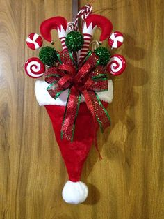 Best 11 For those who think outside the box, this is a different take on the traditional Santa Hat. This plush hat is filled with assorted Christmas picks, elf legs and a wired ribbon bow. May vary slightly from picture. A perfect way to greet your guests Christmas Picks, Noel Christmas, Christmas Projects, Christmas Ornaments, Christmas Ideas, Christmas Crafts For Adults, Christmas Swags, Burlap Christmas, Primitive Christmas