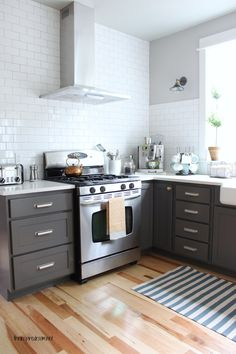 Love the cabinet colors. Kitchen remodel with painted charcoal lower and white upper cabinets, white subway tile and planked walls. Mixed polished nickel, gold and mercury glass knobs and pulls. Before and after pictures! Grey Kitchen Cabinets, Kitchen Cabinet Colors, Painting Kitchen Cabinets, Kitchen Paint, Kitchen Redo, Upper Cabinets, New Kitchen, Kitchen Remodel, Kitchen Layout