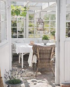 I love the suspended birdcage and the mix of whites and neutrals with all the green.